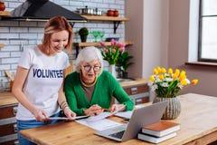 De charmante sociale vrijwilligers tonende presentatie van de gepensioneerdelening op laptop royalty-vrije stock afbeelding