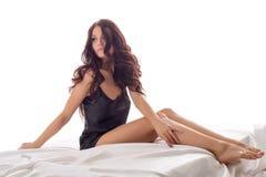 De charmante vrouw zit met haar voeten die van bed bengelen Royalty-vrije Stock Afbeelding