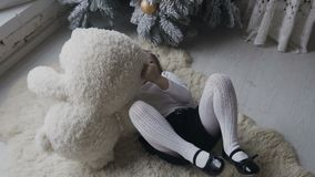 De charmiga flickalögnerna på en mjuk vit matta och spelas med en stor flott björn vinter för snow för pojkeferielay jul min vers arkivfilmer