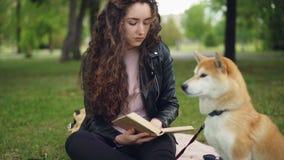 De Cheefulstudent leest boekzitting in het park dan tikkend aanbiddelijk puppy en het glimlachen Houdende van intelligente dieren stock video