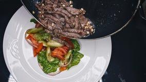 De chef-kok beëindigt lapje vlees van het maaltijd het teasty rundvlees met salade voor gast van restaurant Definitieve aanraking stock footage