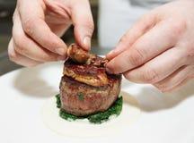 De chef-kok bedekt lapje vlees met foiegras Stock Foto's