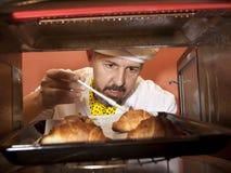 De chef-kok bereidt croissant in de oven voor Stock Afbeelding