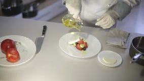 De chef-kok bereidt een Griekse salade in de keuken voor stock videobeelden