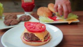 De chef-kok bereidt een hamburger met uien voor