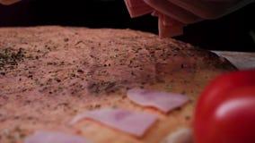 De chef-kok bereidt een pizza voor, zettend ingrediënten op het deeg Kader Het traditionele koken van Italiaanse pizza stock videobeelden