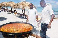 De chef-kok bereidt een reuzezeevruchtenpaella op strand Varadero dichtbij voor zonnebadend toeristen stock foto