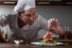 De chef-kok bereidt een snack met mozarella en gerookt vlees voor stock afbeeldingen