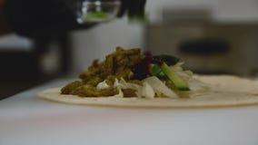 De chef-kok bereidt een tortilla voor Sluit omhoog stock video