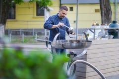 De chef-kok bereidt mosselen in een grote pan op de straat voor royalty-vrije stock foto