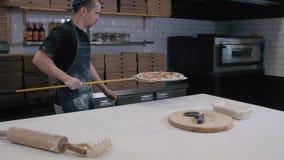 De chef-kok bereidt pepperonispizza in de oven, mening van de rug voor volg Het koken in de oven stock video