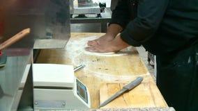 De chef-kok bereidt pizza met kaas en worst voor