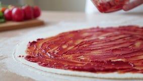 De chef-kok bereidt de pizza voor Dun deeg De keuken in het restaurant De tomaten, kaas, worst, tomatenpuree stock video