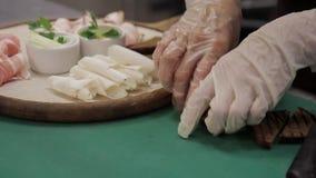 De chef-kok bereidt plaat met divers soort vlees in de restaurantkeuken voor stock video