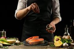 De chef-kok bereidt verse zalmvissen, Cmgu-forel voor, bestrooit met zwarte kruidige peper met ingrediënten Het voorbereiden van  stock fotografie