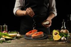De chef-kok bereidt verse zalmvissen voor, smorguforel, die zout bestrooien met de ingrediënten Vorst het bevriezen in de lucht H stock fotografie