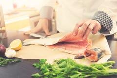 De chef-kok bereidt zalm met kruiden en kruiden voor het koken voor Stock Foto's