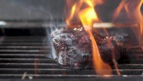 De chef-kok bestrooit peper op het vlees met het been op de grill Veel brand Langzame motie, close-up