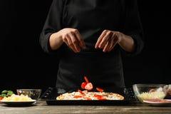 De chef-kok bestrooit pizza met kersentomaten Vorst in motie Conceptie van heerlijk voedsel en gezond voedsel Op een zwarte achte stock afbeeldingen