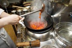 De chef-kok beweegt groenten met zure saus in wok Royalty-vrije Stock Foto's