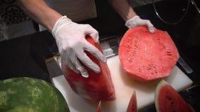 De chef-kok bij restaurant snijdt een grote rode watermeloen stock videobeelden