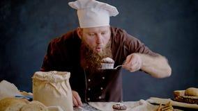 De chef-kok blaast gepoederde suiker van vers voorbereide muffin weg stock video