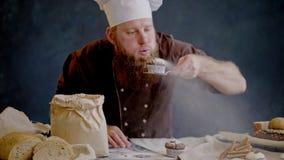 De chef-kok blaast gepoederde suiker van vers voorbereide muffin weg stock videobeelden