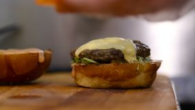 De chef-kok bouwt een hamburger stock video