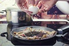 De chef-kok breekt ei in pan, kookt bacon en de gebraden eieren in pan, kookt in keuken, dichte eerlijke mening royalty-vrije stock foto
