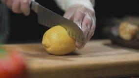 De chef-kok Cuts de citroen op een houten raad stock videobeelden