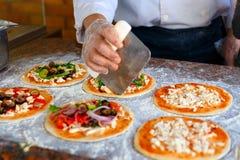 De chef-kok, die bovenste laagjes op een pizza zet Royalty-vrije Stock Afbeelding
