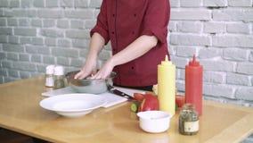 De chef-kok die een salade voorbereiden, die het voorstellen in een restaurantkeuken 4k stock footage