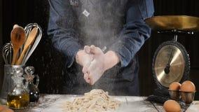 De chef-kok die handen met bloem slaan terwijl het maken van deeg voor pizza, deegwaren, het bakken paneert en gebakjesnoepjes La stock footage