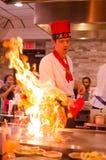 De chef-kok die van het Hibachirestaurant maaltijd voorbereiden en gasten onderhouden royalty-vrije stock afbeelding