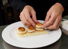 De chef-kok dient foie gras met geroosterde kammosselen Stock Foto