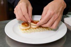 De chef-kok dient foie gras met kammosselen Royalty-vrije Stock Afbeelding