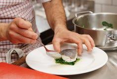 De chef-kok dient gekookte zeebaars Royalty-vrije Stock Foto's