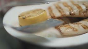 De chef-kok dient geroosterde Pijlinktvis met dicht omhoog citroen stock footage