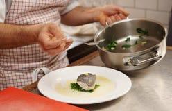 De chef-kok dient gestoomde zeebaars Stock Afbeelding