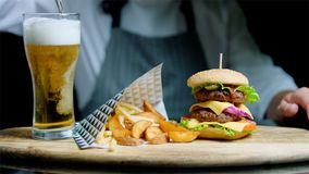 De chef-kok dient reeks van smakelijk hamburger, frieten en bier op het houten dienblad op de zwarte achtergrond Stock Foto's