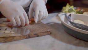 De chef-kok dient witte rubber de kersentomaten van de handschoenenbesnoeiing met groot mes in en zette hen in kom met vissen en  stock video
