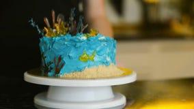 De chef-kok draait cake die op tribune in keuken van restaurant zich binnen bevinden stock videobeelden