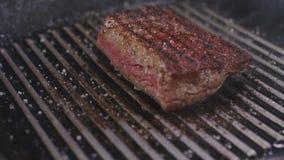 De chef-kok draait het vlees in een pan stock footage