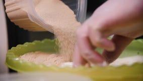 De chef-kok giet bruine suiker in deeg Voorraadlengte De close-up van chef-kok giet en kneedt met de hand vloeibaar mengsel voor  stock videobeelden