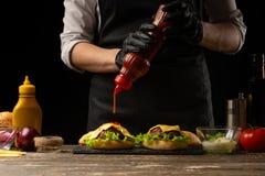 De chef-kok giet een cupcake, hamburgersaus, op de achtergrond van de ingrediënten Horizontale foto, Smakelijk en ongezond voedse royalty-vrije stock afbeeldingen