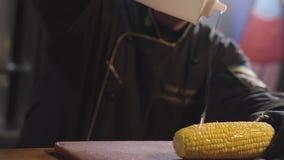 De chef-kok giet graanhoofd met been met stroop dicht omhoog opheffend fles hoog Kok in zwarte robe en het rubberhandschoenen kok stock videobeelden