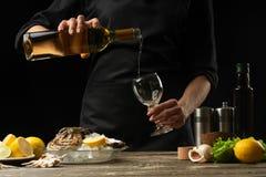 De chef-kok giet, proeft Italiaanse droge oesterwijn met citroen royalty-vrije stock afbeelding