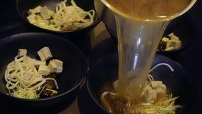 De chef-kok giet vleesbouillon en het voorbereiden van miso soep in Koreaans restaurant stock videobeelden
