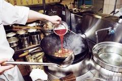 De chef-kok giet zure saus in wok Royalty-vrije Stock Foto
