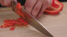 De chef-kok hakt en hakt groentenpeper fijn alvorens te koken stock videobeelden
